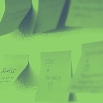 Sticky notes hanging on a wall. The photo has a bright green overay.