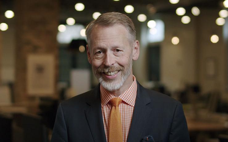 Jim VanderMey, CIO at OST, in a dark gray suit, orange shirt, and orange tie