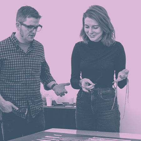 A man and a woman smiling as they look down at a table with pieces of paper connected by string. The woman is holding more strings and tape in her hands.