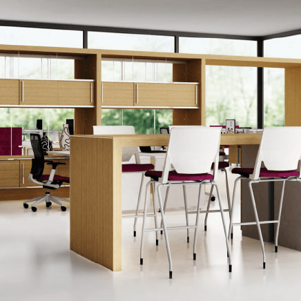 Open plan working space featuring a high-top working desk and stools, as well as desks, chairs and storage in front of windows in the background