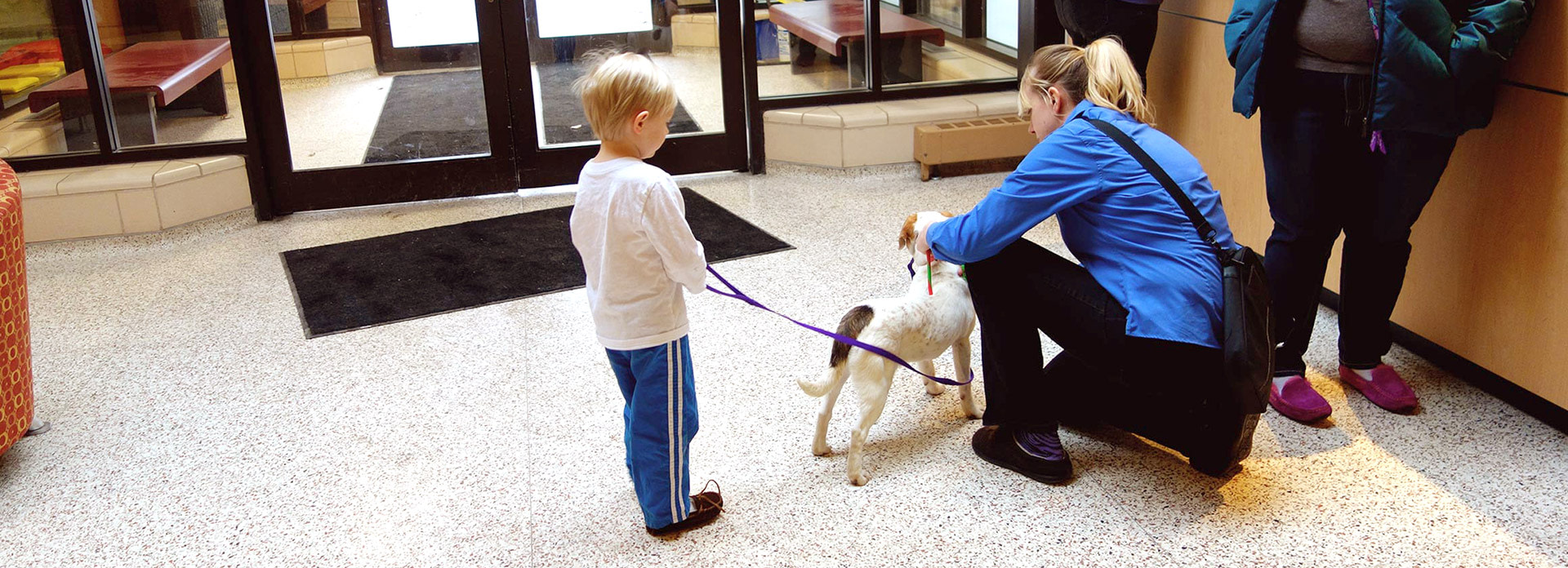 A little boy standing with a dog on a leash. His mother is kneeling down petting the dog.