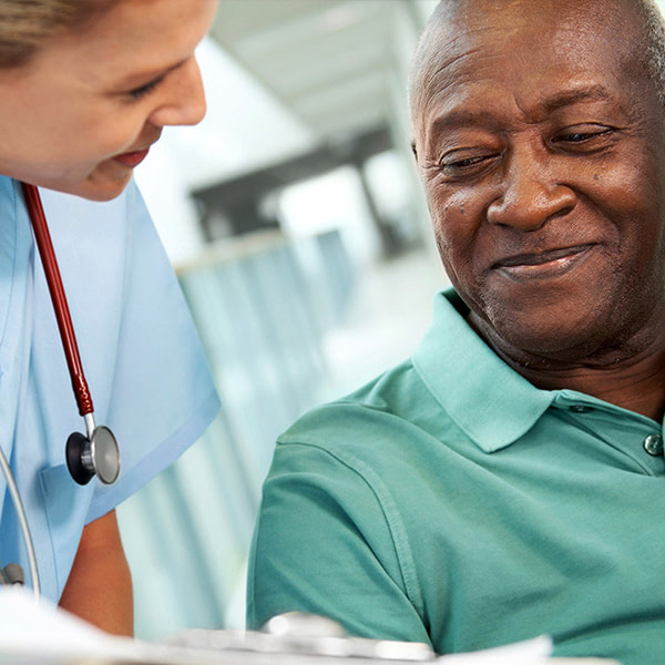 A healthcare working with a stethoscope around her neck bending down to discuss paperwork with a patient. The patient is elderly, smiling, and wearing a green polo shirt.